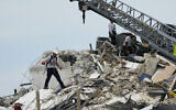 Rescue worker walk among the rubble where a wing of a 12-story beachfront condo building collapsed, Thursday, June 24, 2021, in the Surfside area of Miami. (AP/Lynne Sladky)
