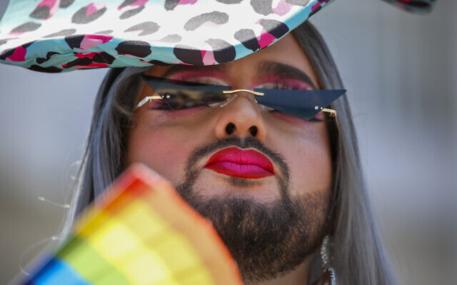 A participant pauses in the annual Pride Parade, in Tel Aviv, Israel, Friday, June 25, 2021. (AP Photo/Ariel Schalit)