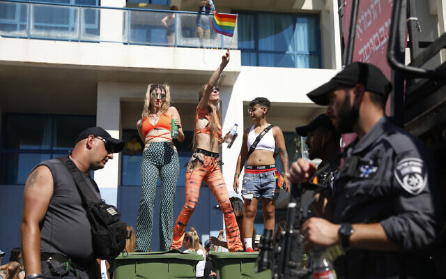 Revelers dance on garbage bins as police stand guard at the annual Pride Parade, in Tel Aviv on June 25, 2021. (AP Photo/Ariel Schalit)