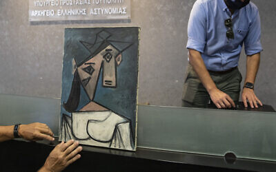 A cubist female bust by the Spanish painter Picasso is displayed by police officers in Athens during a press conference on June 29, 2021. (AP Photo/Petros Giannakouris)