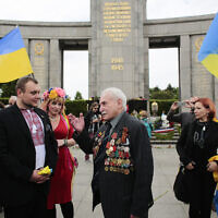 Soviet war veteran David Dushman, 92, center, talks to people holding Ukrainian flags as he attends a wreath laying ceremony at the Russian War Memorial in the Tiergarten district of Berlin, Germany, May 8, 2015. (AP Photo/Markus Schreiber)
