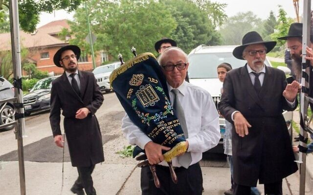 Leon Oliwkowicz carries a Torah scroll at a dedication ceremony in Chicago in 2019. (Courtesy Chabad)