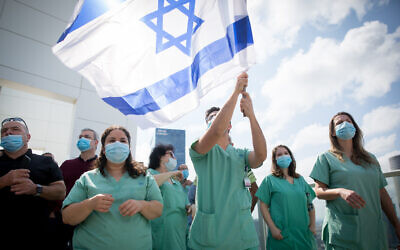 Israeli medical staff cheer an Israeli airforce acrobatic team flying over Ichilov hospital in Tel Aviv on Israel's 72nd Independence Day, April 29, 2020 (Miriam Alster/Flash90)