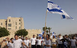 Young Jewish men dance with Israeli flags near Jerusalem's Old City on Jerusalem Day, May 10, 2021. (Nati Shohat/Flash90)