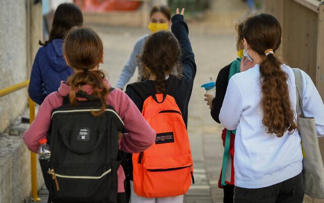 Illustrative: Israeli schoolkids wearing face masks return to school in Tel Aviv on February 11, 2021. (Avshalom Sassoni/Flash90)
