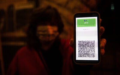 Illustrative image: A woman shows her green pass as she arrives to watch a play at the Khan theater in Jerusalem, on February 23, 2021. (Yonatan Sindel/Flash90)