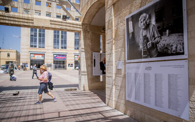 People walk past a photo exhibition of the last survivors of the Holocaust as part of the 'Lonka project,' at Safra Square in Jerusalem, April 8, 2021. (Yonatan Sindel/Flash90)
