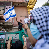 Palestinians and left wing activists protest against the eviction of Palestinian families from their homes in the East Jerusalem neighborhood of Sheikh Jarrah, on April 16, 2021. (Yonatan Sindel/Flash90)