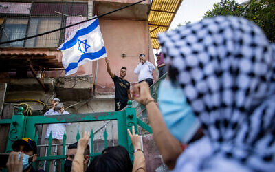 Palestinians and left wing activists protest against the eviction of Palestinian families from their homes in the East Jerusalem neighborhood of Sheikh Jarrah, April 16, 2021. (Yonatan Sindel/Flash90)