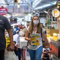 People shop, some wearing face masks at the Mahane Yehuda market in Jerusalem, May 26, 2021. (Olivier Fitoussi/Flash90)
