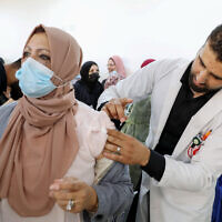 Palestinians receive the Pfizer-BioNTech COVID-19 vaccine in the West Bank city of Hebron, March 27, 2021 (Wisam Hashlamoun/Flash90)