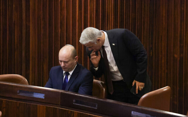 Head of the Yamina party Naftali Bennett (left) and head of the Yesh Atid party Yair Lapid seen in the plenum hall of the Knesset during the voting in the presidential election, in Jerusalem, June 2, 2021. (Olivier Fitoussi/Flash90)