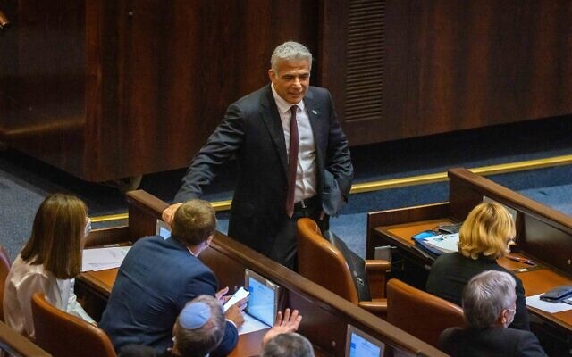Head of the Yesh Atid party MK Yair Lapid, center, seen in the plenum hall of the Knesset in Jerusalem, June 2, 2021. (Olivier Fitoussi/Flash90)