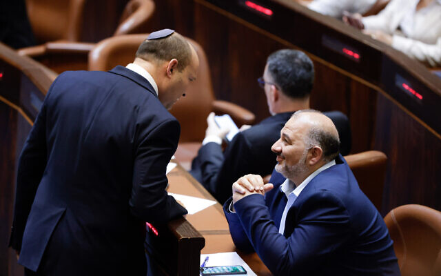 Prime Minister Naftali Bennett, left, and Ra'am leader MK Mansour Abbas, seated, at the swearing in of the new Israeli government, in the Knesset on June 13, 2021. (Olivier Fitoussi/Flash90