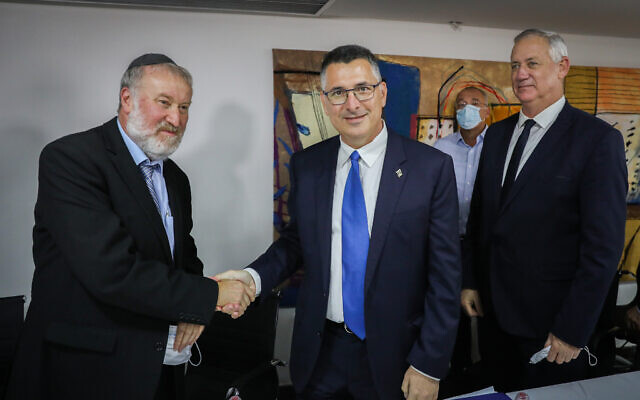 Then-newly appointed Justice Minister Gideon Sa'ar with Attorney General Avichai Mandelblit (left) and then-outgoing minister of justice Benny Gantz (right) at a ceremony marking the change of minister, at the Ministry for Justice in Jerusalem on June 14, 2021. (Olivier Fitoussi/Flash90)