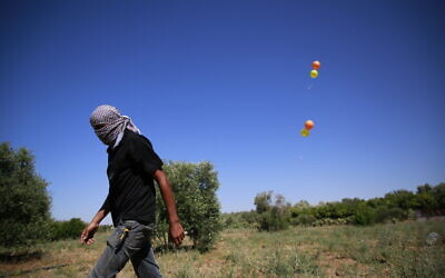 Masked Palestinian members of the Islamic Jihad terror group launch incendiary balloons from Gaza toward Israel on June 15, 2021. (Atia Mohammed/FLASH90)