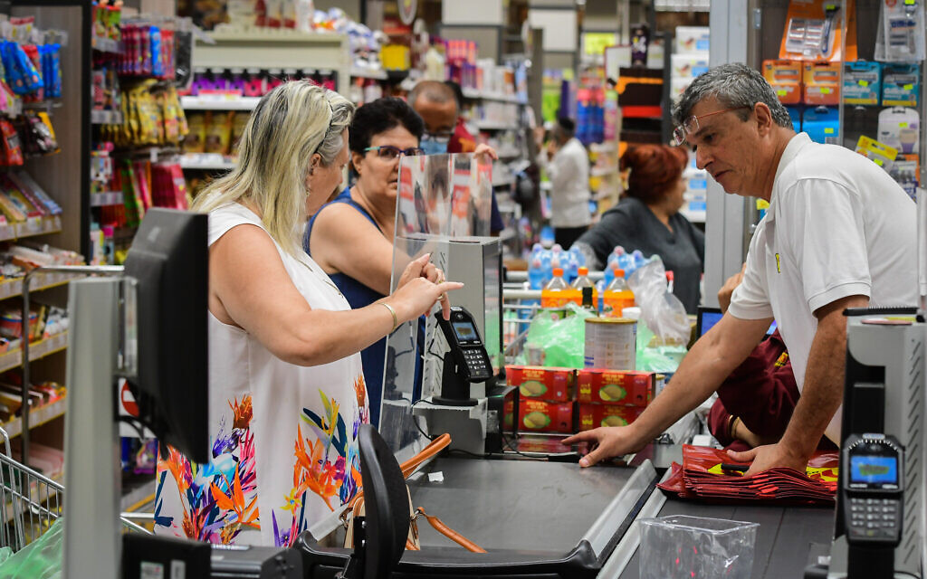 People shop at the Yochananof supermarket in Tel Aviv on June 14, 2021, after the Health Ministry announced the end of the COVID-19 obligation to wear a mask in closed public places. (Avshalom Sassoni/Flash90)
