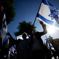 Jewish men dance with Israeli flags during the March of Flags near Jerusalem's Old City, June 15, 2021. (Yonatan Sindel/Flash90)