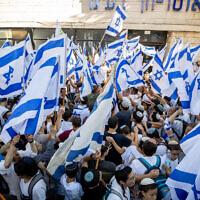 Nationalist Israeli Jews hold Israeli flags and dance near Jerusalem's Old City, June 15, 2021. (Yonatan Sindel/Flash90 )
