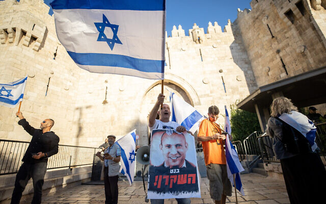 """An Israeli man waving a flag holds a poster calling Prime Minister Naftali Bennett """"the liar,"""" during the nationalist flag march, at the Damascus Gate in Jerusalem's Old City, June 15, 2021. (Yonatan Sindel/Flash90)"""