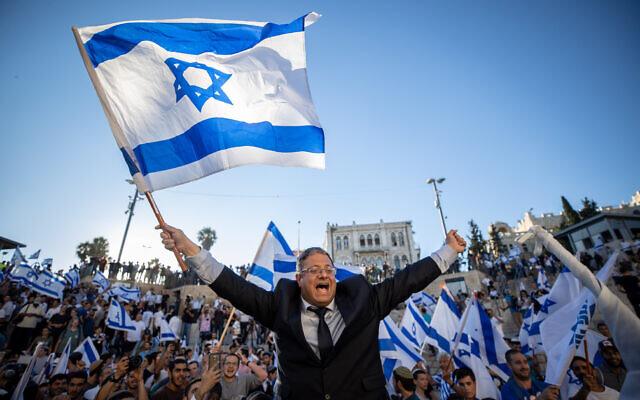 Far-right MK Itamar Ben Gvir dances with an Israeli flag at the Damascus Gate in Jerusalem's Old City, June 15, 2021. (Yonatan Sindel/Flash90)