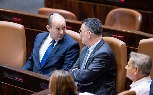 Prime Minister Naftali Bennett with Minister of Justice Gideon Saar during a swearing-in ceremony of new MKs at the Knesset, in Jerusalem, June 16, 2021.(Yonatan Sindel/Flash90)