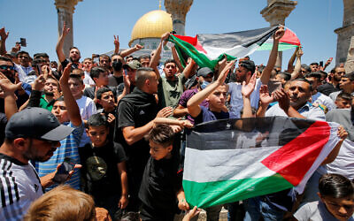 Worshippers raise the Palestinian flag at the Al-Aqsa mosque compound in Jerusalem's Old City on June 18, 2021. (Jamal Awad/Flash90)