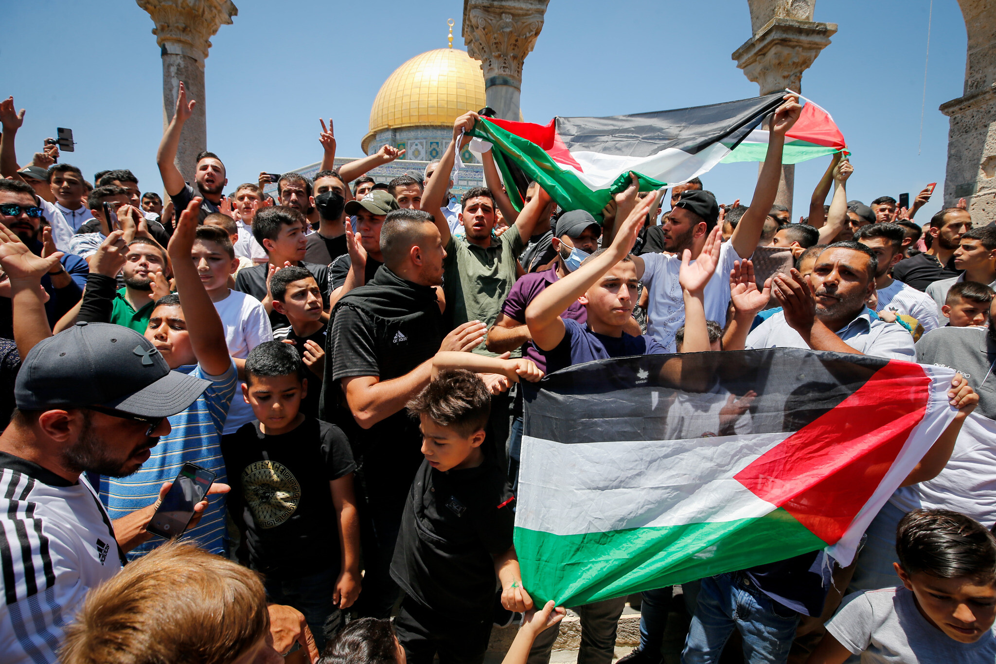 Worshippers raise the Palestinian flag at the Al Aqsa mosque compound in Jerusalem's Old City
