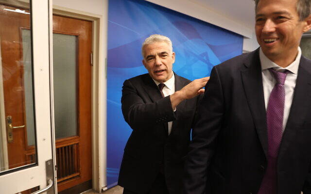Foreign Minister Yair Lapid (left) arrives for the first cabinet meeting of the new government at the Prime Minister's Office in Jerusalem on June 20, 2021. In foreground is Communications Minister Yoaz Hendel. (Amit Shabi/POOL)