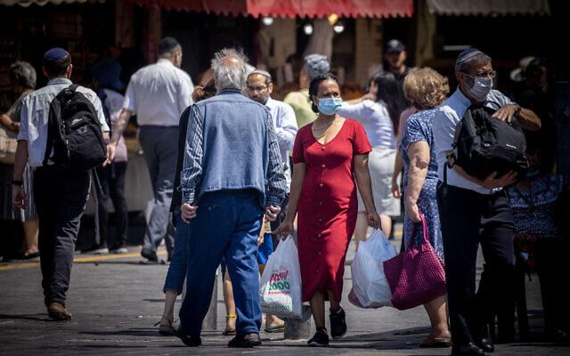 Israelis, some wearing masks, shop at the Mahane Yehuda market in Jerusalem on June 24, 2021. (Yonatan Sindel/Flash90)