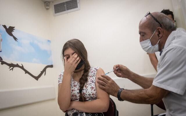 An Israeli teenager received a coronavirus vaccine in Jerusalem, on June 24, 2021. (Yonatan Sindel/Flash90)