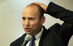 Israeli Prime Minister Naftali Bennett, pictured here in 2014 giving a speech, holds his kippa to his head. (Menahem Kahana/AFP)