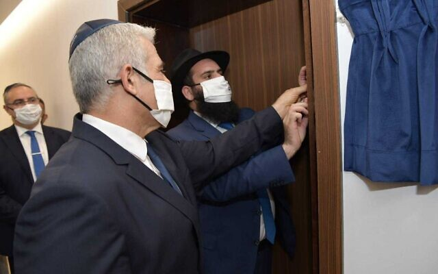 O ministro das Relações Exteriores Yair Lapid (L) e o rabino Chabad Levi Duchman instalam uma mezuzá durante a inauguração da embaixada israelense em Abu Dhabi, em 29 de junho de 2021. (Shlomi Amsalem / GPO)