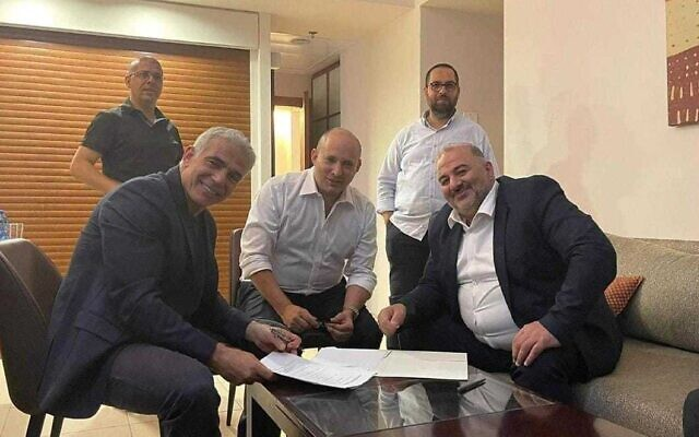 Yesh Atid leader Yair Lapid (L), Yamina leader Naftali Bennett (C) and Ra'am leader Mansour Abbas sign a coalition agreement on June 2, 2021 (Courtesy of Ra'am)