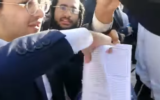 Haredi extremists tare up prayer book of Women of the Wall worshippers at the Wetern Wall on June 11, 2021. (Screen capture/Facebook)