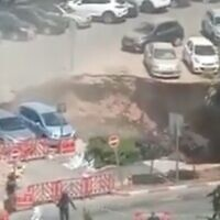 Screen capture from video of a sinkhole that opened in the parking lot of the Shaare Zedek Medical Center in Jerusalem, June 7, 2021. (Twitter)