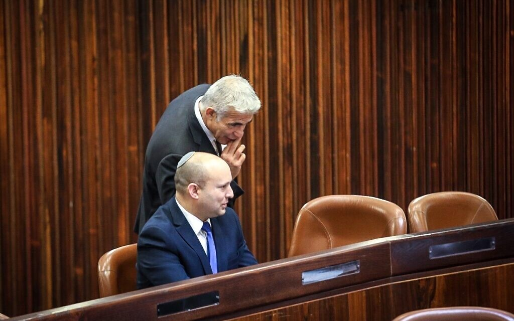 Yesh Atid chairman Yair Lapid (standing) and Yamina head Naftali Bennett in the Knesset plenum for the election of Israel's 11th president, June 2, 2021. (Dani Shem Tov/ Knesset)