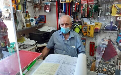 Shai Berlin  behind a newly re-erected Perspex screen in his hardware store in Binyamina on June 21, 2021 (Nathan Jeffay/Times of Israel)