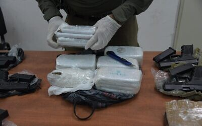 An Israeli investigator unwraps bricks of hashish smuggled into the country from Lebanon on June 2, 2021. (Israel Defense Forces)