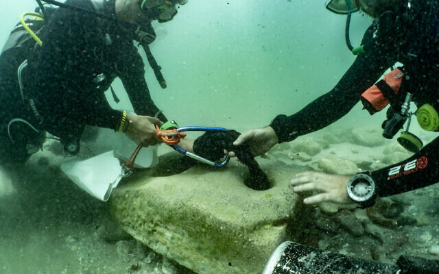 In this handout photo from June 10, 2021, scuba divers with an ancient stone anchor that was found at the Tel Dor archaeological site in northern Israel. (Amir Yurman of the University of Haifa's Maritime Workshop)