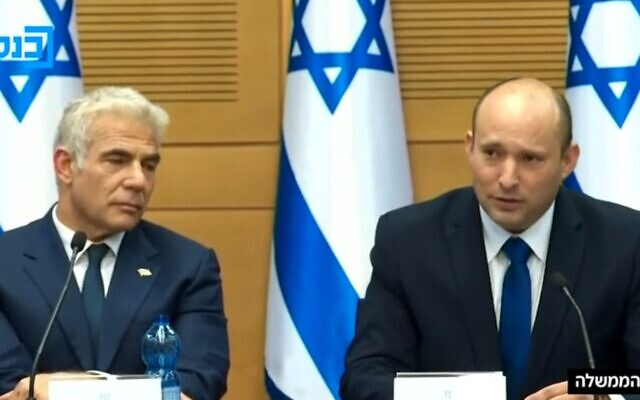 Prime Minister Naftali Bennett addresses his first cabinet meeting, with Alternate PM Yair Lapid at his side, June 13, 2021. (Channel 12 screenshot)