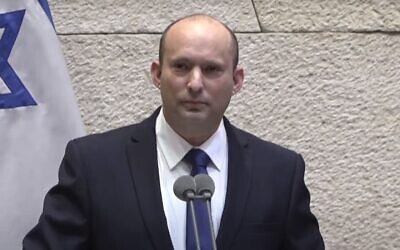 Prime Minister-designate Naftali Bennett pauses amid heckling of his speech to the Knesset, June 13, 2021 (Knesset channel screenshot)