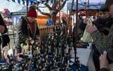 Customers at a Krakow market buy figurines of Hasidic Orthodox men. (Jason Francisco via JTA)
