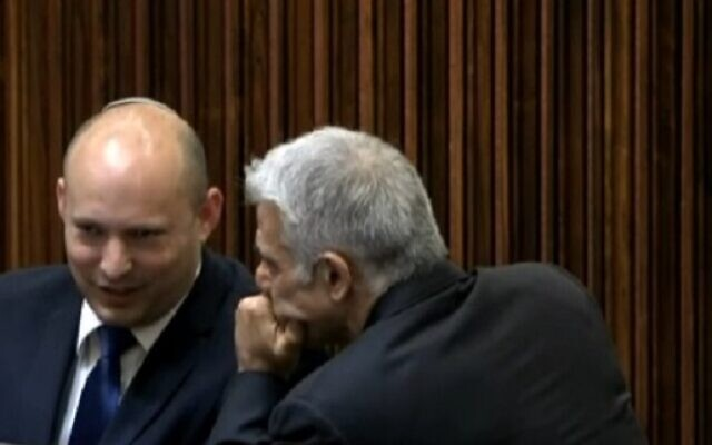 Yamina chief Naftali Bennett and Yesh Atid leader Yair Lapid seen conversing in the plenum on June 2, 2021, hours before Lapid's mandate to form a government expires (video screenshot)
