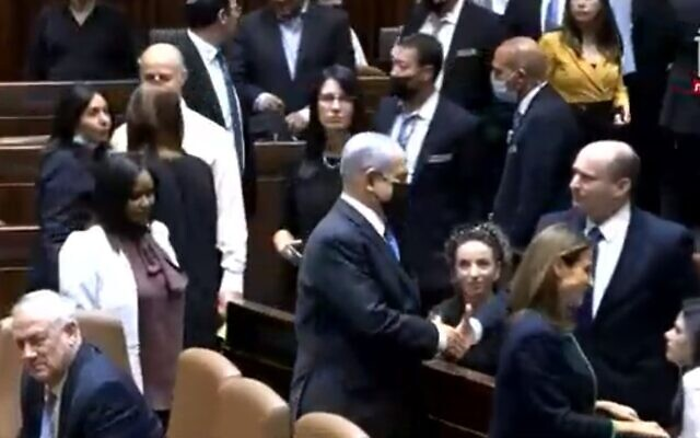 Outgoing prime minister Benjamin Netanyahu shakes hands in the Knesset with newly elected Prime Minister Naftali Bennett, June 13, 2021 (Channel 12 screenshot)