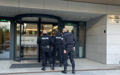 Police enter a building on May 11, 2021, in connection with an 'action day' against alleged investment fradusters. (Rheinland Pflaz Police)