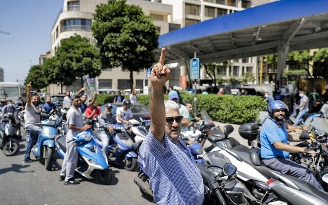 Scooter drivers waiting outside a gas station in Lebanon's capital Beirut raise their middle fingers in protest against hikes in the price of fuel, June 29, 2021. (Joseph Eid/AFP)