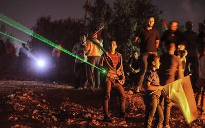 Palestinian protesters use laser torches during a demonstration against the Israeli settlers' outpost of Evyatarin the West Bankon July 1, 2021.  (Photo by JAAFAR ASHTIYEH / AFP)