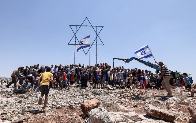 Settlers gather for a group photograph under a giant Star of David and a national flag before evacuating the newly-established wildcat outpost of Evyatar near the northern Palestinian city of Nablus in the West Bank, on July 2, 2021 (Emmanuel DUNAND / AFP)