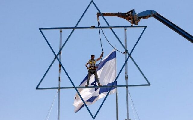 An Israeli settler adds the finishing touches to a large Star of David before evacuating the newly-established wildcat outpost of Evyatar in the West Bank, on July 2, 2021.(Photo by Emmanuel DUNAND / AFP)